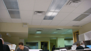 Typical office lighting fixture installation in suspended ceiling grid.